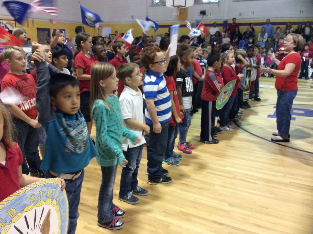 Students singing and celebrating at a Veteran's Day rally