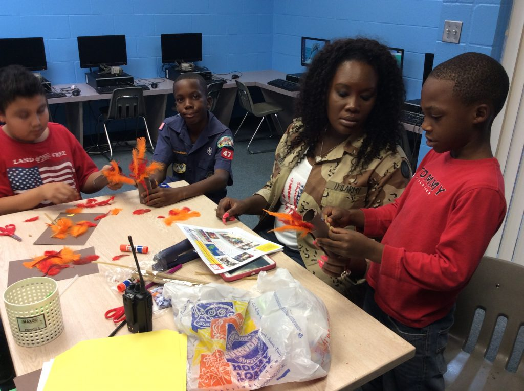 Teacher assisting students with arts and crafts